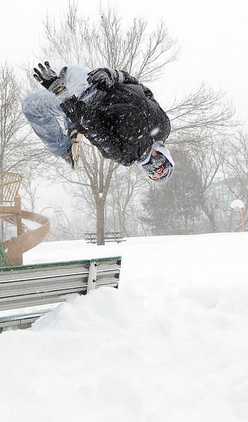 Michael Williams, 13, does a back flip off a bench in Lionel P. Potvin Park on Cedar Street in Lewiston Wednesday morning as he and a friend were enjoying the day off from school.