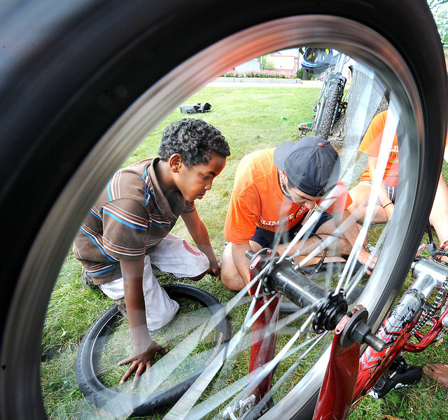 "Brad Samuels of Andover, Ma., a member of New England Climate Summer, a summer internship program for college students interested in biking, community organizing, climate justice and a sustainable future, helps Askar Husseinn, 10, of Lewiston, fix a flat tire on his bicycle in Kennedy Park Saturday afternoon.  Husseinn was one of a number of area youth's who took part in the ""Care for Your Bike-Care for Our Planet"" clinic."