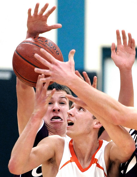 Edward Little's Ian Therriault, left, and Bowne Leary, unseen at right, team up to strip the ball from Brunswick's Alex Ouellette during first half action of Monday night's game in Brunswick.