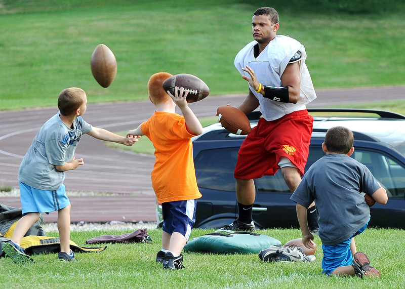 Teven Colon, former Edward Little football player and current running back for the Maine Shrine Lobster Bowl Classic East team, defends himself from an onslaught of footballs being thrown at him by several of the coaches children during a break in Tuesday's practice at Hebron Academy.  For more on the game, turn to the sports section.