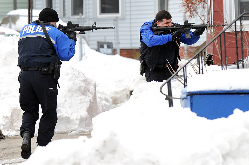Auburn Police officers cover each other as they get into position to seal off the area around 33 Pine Street in Auburn Saturday afternoon where a man with a shotgun is holding police at bay.  Police received a call from a woman who reported being threatened by the man.