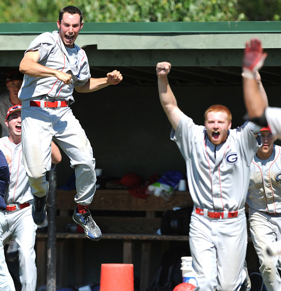 Gayton's Joe Sullivan, left and Jeff Keene, right and other players celebrate as teammate Chris Jacques crosses the plate to score the winning run in the bottom of the 9th inning as the team came back from a two run deficit in the inning to beat Brewer and advance to the championship game later in the afternoon.