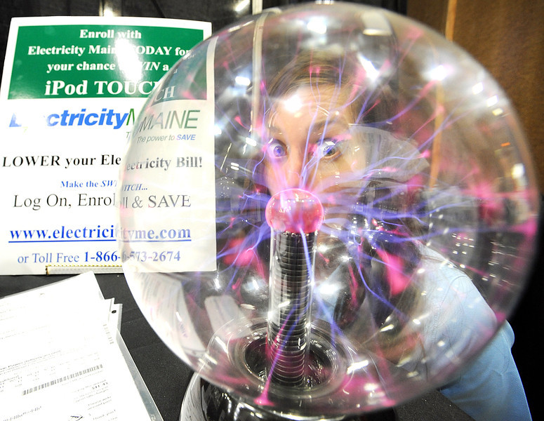 Danielle Beckwith fro ElectricityMAINE looks through a plasma ball at her booth Saturday afternoon in the Androscoggin Bank Coliess in Lewiston during the Maine Home Show.  The show continues through Sunday with dozens of local vendors displaying their products.