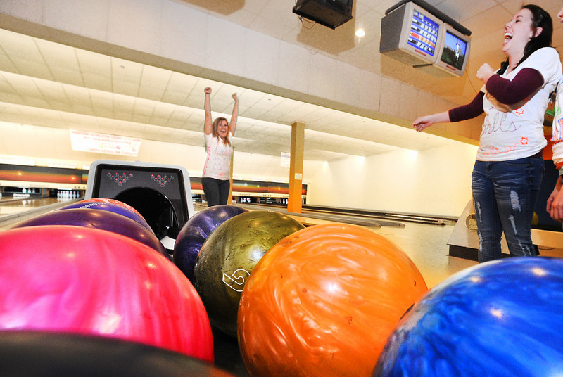 Jami Childs of Poland, left celebrates a strike with her teammate, Samantha Marquis during Saturday's Big Brothers Big Sisters Bowl For Kids' Sake at Sparetime Recreation Center Center.  The 15th annual fundraiser has grown so much that it takes place over two days to accomodate all the teams that want to participate.  Hannah Goodenow and Amber Crocker of Freeport round out the Dolls with Balls team, former classmates that get together every year to continue the tradition that not only helps raise money for a good cause, but a good way to keep their friendship alive.