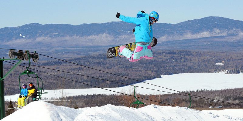 Colby Wheaton, 17 of Phillips flies over a jump at Saddleback Mountain Wednesday afternoon as he and thousands of others around the state enjoyed a picture perfect day to play in the snow, many on vacation from school.