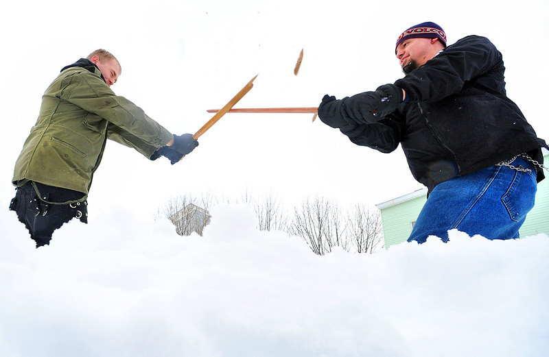 The practice Katana Stick of Mike Hayward, left, shatters as he and friend Josh Levasseur duel in a snow covered field at the corner of Blake and Maple Streets in Lewiston Friday afternoon.