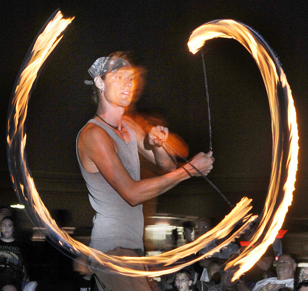 Bri Maneely of Bangor juggles fire Friday night at the Great Falls Balloon Festival at Simard-Payne Park . Several performance artists from Aether Arts entertained the crowd between bands.