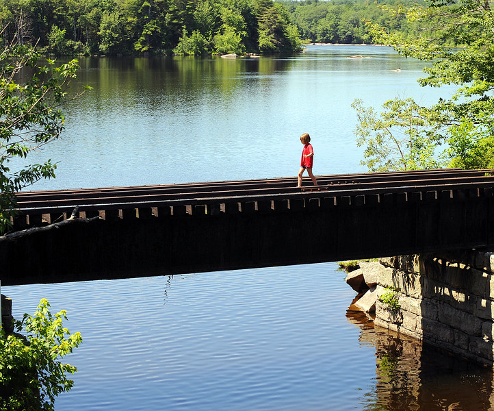 An unidentified young girl carefully makes her way across the abandoned railroad trestle crossing the Sabattus River where it meets the Androscoggin River in Lisbon Sunday morning as she looks for a better vantage point to watch the finish of the 13th Annual Chief Worumbo Androscoggin River Race.  According to race officials, walking across the trestle is not against the law and often a place where people come to fish.