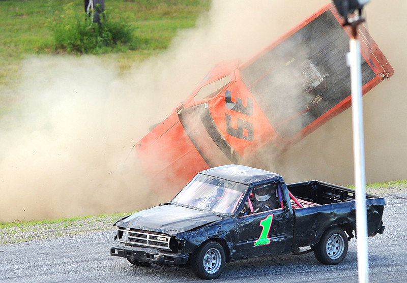 Corey Williams of Sumner goes end over end as he slides off the track at Oxford Plains Speedway Friday night during the sport truck race.  John Lizotte of Mechanic Falls foreground, motors past as the yellow flag comes out.  Williams crawled out of his truck and waved to crowd to signal he was ok.