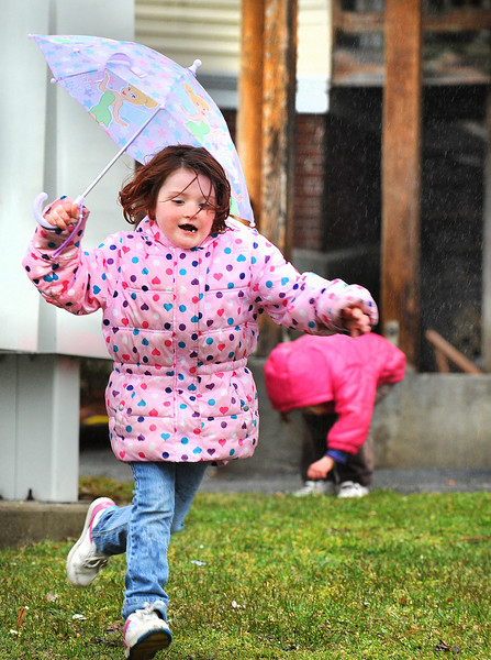 Heather Emerson Jr. 7, of Lewiston plays in the rain with her siblings and family friends at the corner of Knox and Birch Streets in Lewiston while walking home from school with her mother in the rain Tuesday afternoon
