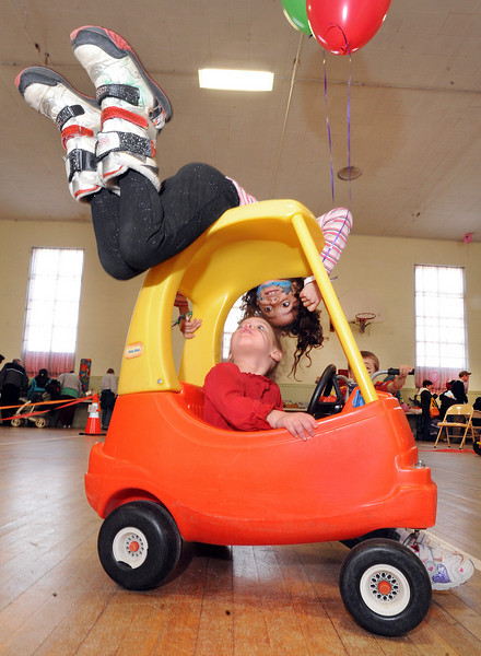 Kiesha Edwards, 2, of Lewiston peeks up at her friend Jaymie Day, 7 of Lewiston at the Toy Library in Lewiston Saturday morning during the Second Annual Toy Library SHAREcenter Trykes for Tykes Fundraiser.  Trycle's and other modes of children transportation were provided to pedal and push around in a circle in the middle of the gym as other activities went on nearby.  Raffles, food and drinks were provided with a karate demonstration, puppet show, dance with face painting