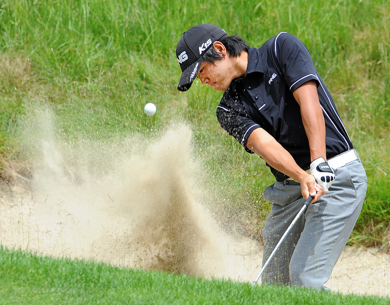 Beon Yeong Lee of Canada blasts out of the sand trap onto the 5th green during the final round of the Charlie's Maine Open Pro Am golf tournament at the Falmouth Country Club Wednesday.  Lee rolled the shot within a foot of the hole to make par.