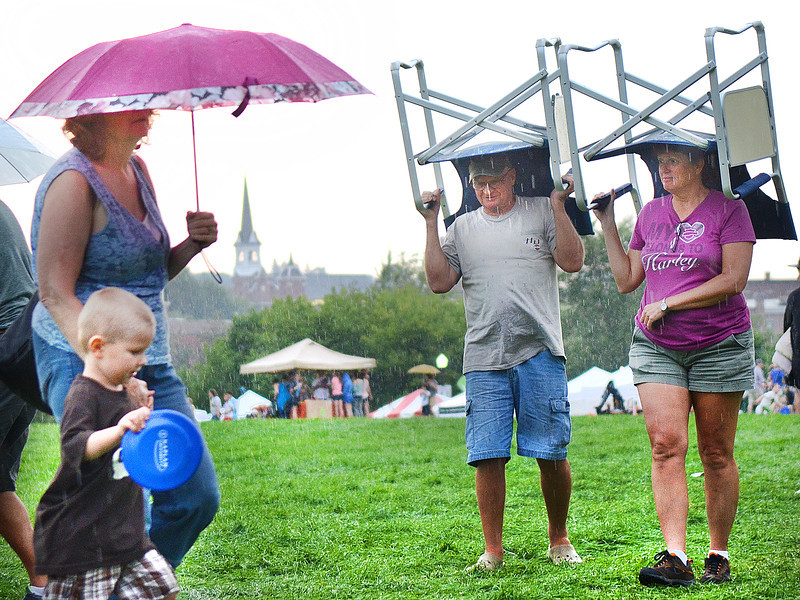 People rush for cover as the rain begins to come down Friday night, ending what little hope there was that the balloons might launch.  Oliver and Cindy Clair, right, use their chairs as makeshift umbrellas.  The Cliars, from Meridian Mississippi, came to check out the balloon festival.