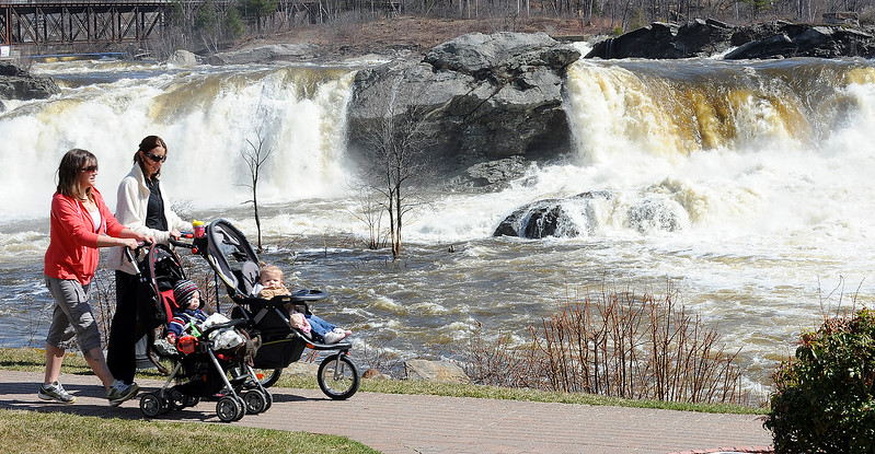 Allie Keene and Reagan, 8 mos., from Poland,  take a walk with friends Tara Averill and her daughter, Aniston, 1, from Hartford, along the Riverwalk in Auburn Thursday morning.  They usually walk in a different spot, but with Great Falls roaring, they decided on going to Auburn to walk and play at Bonney Park.