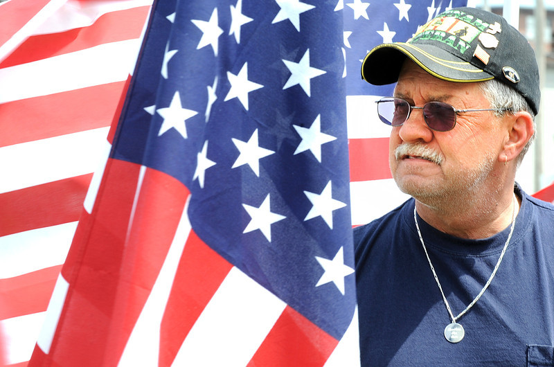 "Stan Carmichael of Lewiston, looks out at the 400 flags at Simard-Payne Memorial Park in Lewiston Sunday morning.  A veteran of three tours of duty in Vietnam, Carmichael said, ""I was one of the lucky ones that came back.  It's really hard standing here.""  He bought a flag in honor of his father, a WWII veteran who was in the Battle of the Bulge.  The display of 400 flags, described as a ""Field of Honor"", is a fundraiser for the Auburn Exchange Club. The civic group hopes to raise money by selling all of the 400 flags at $40 each. Proceeds will fund its charity work."