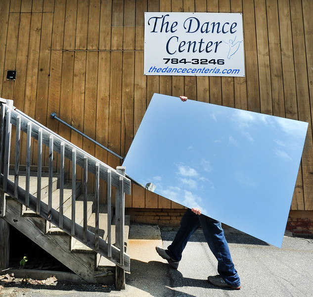 One of several workers from Creative Glass Company in Lewiston carries a mirror to be used at The Dance Center's new location on Western Avenue in Auburn.  Several small businesses are being forced to vacate the former Great Falls School as it is being torn down.  Dance Center LA owner Elizabeth Hansen and her husband bought the former Merrill Hill School at the corner of Court Street and Western Avenue and are busy renovating it. They plan to move the dance center into the building in June, taking a few of their Great Falls neighbors with them. The Mudroom Pottery Studio and fitness trainer Glenn Atkins will make the move with the Hansens.  They are also contemplating re-opening a day care center in the basement where one was once located..