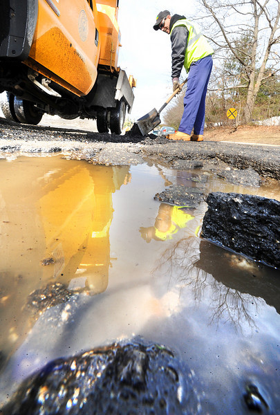 "Lewiston Public Works Department employee Reggie Poussard fills one of a number of potholes on Strawberry Avenue in Lewiston Thursday morning.  Public Works crews throughout the state are busy this time of year repairing damaged roads as the changing tempatures create havoc with the pavement.  ""We used over 8 tons of cold patch on Lincoln Street alone so far this year."" says Poussard.  He also quipped, ""the worst part about it is the traffic.  People complain about the potholes, but when we stop to patch them, they get mad because they have to slow down or stop for a second before going around us.  You just can't win."""