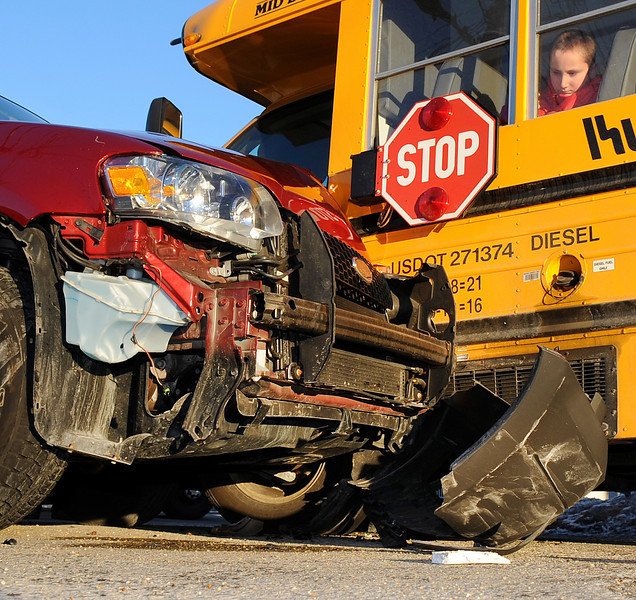 One of several students on a school bus involved in an accident on the corner of Prospect Ave and Lisbon Streets in Lewiston looks at the damage to the SUV that hit it Monday afternoon.