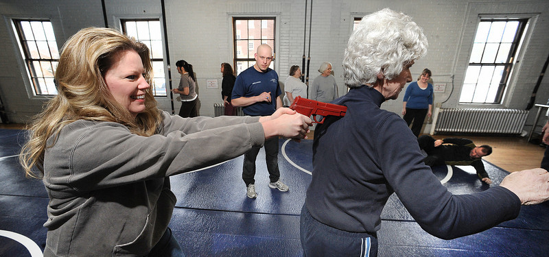 Lewiston Police officer Jason Johnson watches how Patricia Bellegarde, right of Auburn will react to having a gun pointed to her head by Kris Avery of Windham during Saturday's first of a two day Personal Defense Course offered by members of the Lewiston Police Department taking place at the Lewiston Armory.