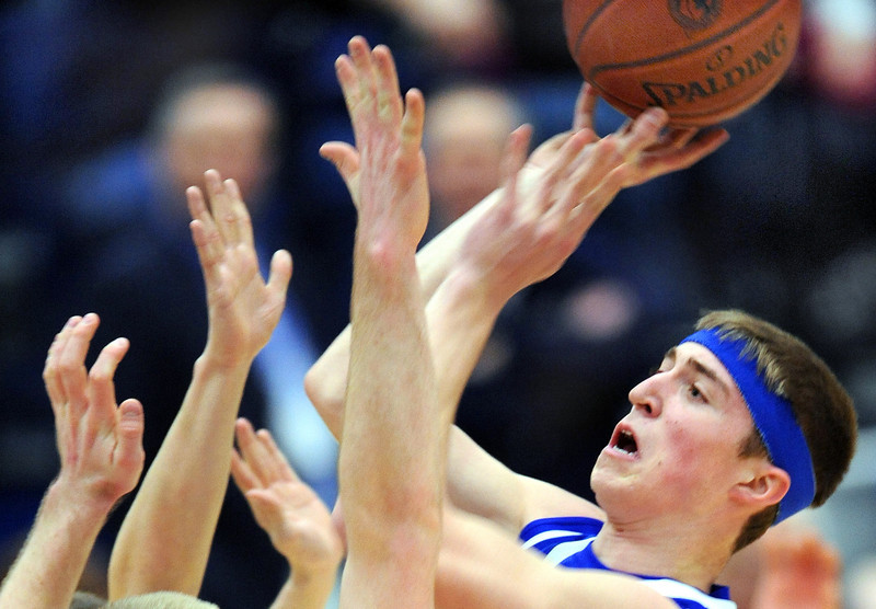 Lewiston's Jake Dumas takes a shot over several outstretched Hampden Academy defenders during first half action from Saturday's Class A East State Invitational Basketball Tournament game between Hampden Academy and Lewiston High School.