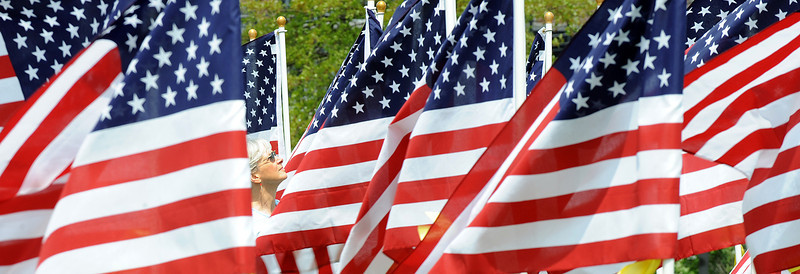 "Elizabeth Gondek of Auburn looks out as the sea of flags Saturday morning at Simard-Payne Memorial Park in Lewiston.  The display of 400 flags, described as a ""Field of Honor"", is a fundraiser for the Auburn Exchange Club. The civic group hopes to raise money by selling all of the 400 flags at $40 each. Proceeds will fund its charity work."