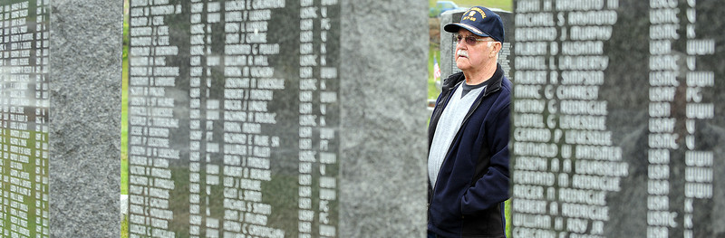 Tom Lufkin of Lewiston, a Korean War veteran, looks for the name of his grandson on one of the memorial stones during Memorial Day activities at Veterans Memorial Park in Lewiston on Saturday morning.