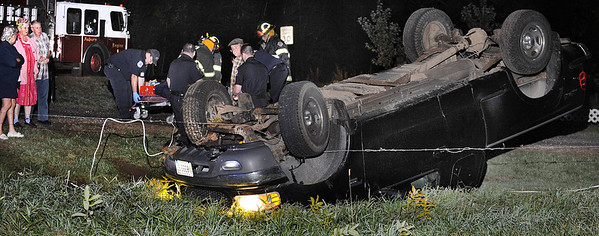 "While United Ambulance paramedics tend to the single occupant of this rolled over truck, Raymond Labrie, plaid shirt, talks with Auburn Police officers about how he was in his house at the corner of South Main Street and South Witham Road in Auburn Monday night when he heard screeching tires and a big bang.  ""It's not the first time, it's happened many, many times."" Labrie said.  Instead of heading back to bed, he had to wait around for the wrecker to haul the truck away and repair the fence so his 3 horses wouldn't ""run all over town."""