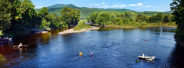 A pair of kayakers paddle down the Androscoggin River in Bethel, as Brett Trefethen, right, rowing his drift boat with his wife Amy and daughter Ella, 8, of Mt. Vernon, making up team Patagonia, is follwed by Scott Stone, of Norway,rowing, and his passenger Kathy DiCocco of Bethel, left, making up the Northern Lights team during the beginning stages of the Notheast Drift Boat Championships.