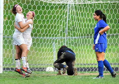 Lewiston's Erica Lemieux, right, watches Edward Little players Kory Norcross, left celebrate with Lexis Clavet after Clavet booted the game winning shot past Lewiston goalie Lix Jimenez, center with a minute and a half left in the game Saturday afternoon in Auburn.