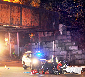 Emergency personel tend to a man who was hit by a truck that fled the scene under the railroad trestle on Turner Street in Auburn Friday night.