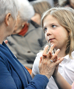 Saint Dominic Academy third grader Charlotte Cloutier, 9, looks up at her grandmother, Pat Chretien, of Lewiston, with adoring eyes while they await the start of a special mass at the Auburn school Wednesday morning.  Grandparents were invited to come into the school and check out the Thanksgiving placements and socialize before a pre-Thanksgiving mass was celebrated.
