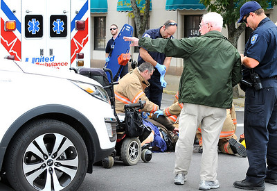 Maurice Dutil of Lewiston, right, talks with LPD officer Brian Rose at the corner of Ash and Park Streets in Lewiston Friday afternoon as Roger Beaudoin lies on the ground.  Beaudoin was crossing the street in his wheelchair when he was hit by Dutil's vehicle, left.  Beaudoin was taken to Central Maine Medical Center with non life threatening injuries.