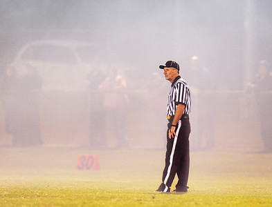 A referee is enveloped in smoke blanketing the field from the grill at the snack shack at Friday night's football game between Messalonskee and Oxford Hills at Gouin Athletic Complex in Paris.