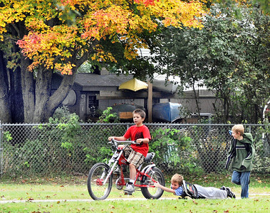 Alex Whitney, riding bike, pulls his friend Harley Isaacs to school on his skateboard Wednesday morning as their friend Alec Treadwell runs behind.  The fourth graders at Walton Elementary School walk or bike to school every day.  Wednesday was International Walk & Bike to school day.