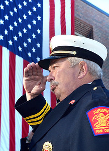 Auburn Battalion Chief Richard McFadden Jr. salutes during the raising of the firefighters flag at Central Fire Station Tuesday morning during a memorial ceremony to remember those who died on September 11, 2001.