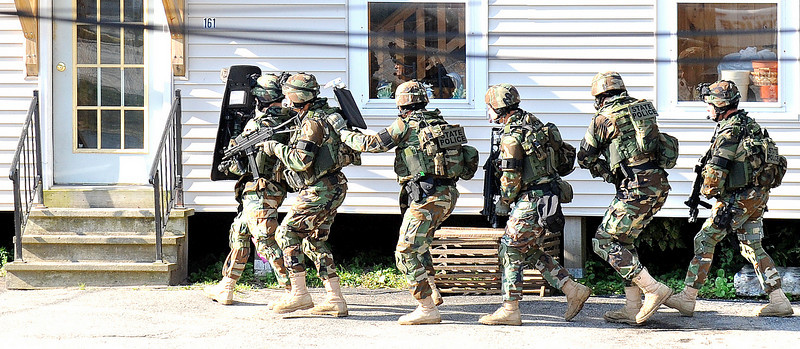"The Maine State Police Tactical Squad prepares to enter 181 Holland Street, which is connected to 181 Holland where a man named Dan was keeping police at bay.  According to family members, a long standing domestic dispute has been going on between the man and neighbors.  Police were at the location yesterday, and this morning at 5am when Justin Lord, 21 of 2 Towle Street, left for work, according to his sister Karen Brown,  the man confronted Justin at the 7-11 just up the street.  He pulled a ""six shooter"" pointed it at his head and cocked the gun.  He said something to Justin, then ran back to his apartment where he is now holed up."