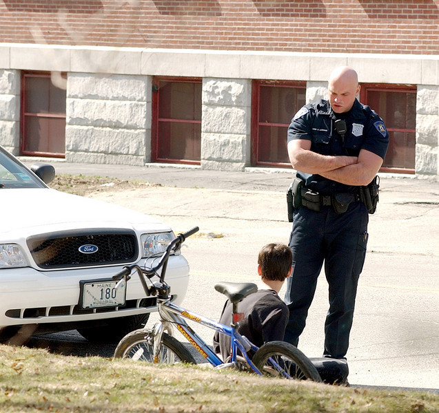 Lewiston police officer David Levesque talks to a youth on Walnut Street in Lewiston after the juvenile allegedly stole this bicycle and bolted over the trestle at Bonney Park in Auburn over to Railroad Park in Lewiston and through Kennedy Park where he was stopped.