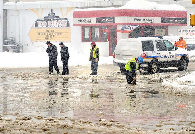 Lewiston Water District's Adam Hart, blue hardhat in foreground, works to unclog a storm grate to help drain thousands of gallons of water that flowed down East Avenue and pooled in the middle of Lisbon Street after a water main broke in front of CVS on East Avenue.