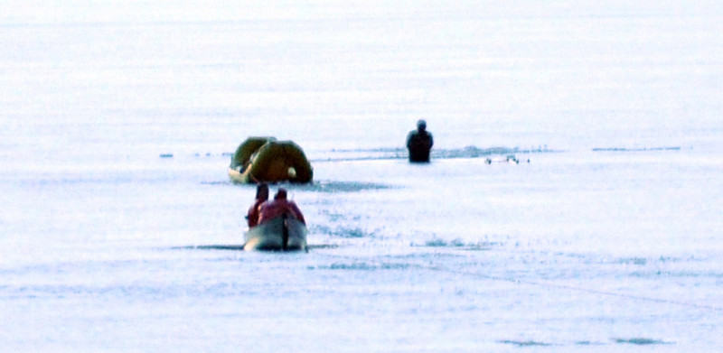John Dudley, right, stands in waist deep water in the middle of Bear Pond after breaking through the ice while cross skiing.  Through sheer luck, he went through above a sand bar where it was shallow enough to be able to stand on the bottom until being rescued.