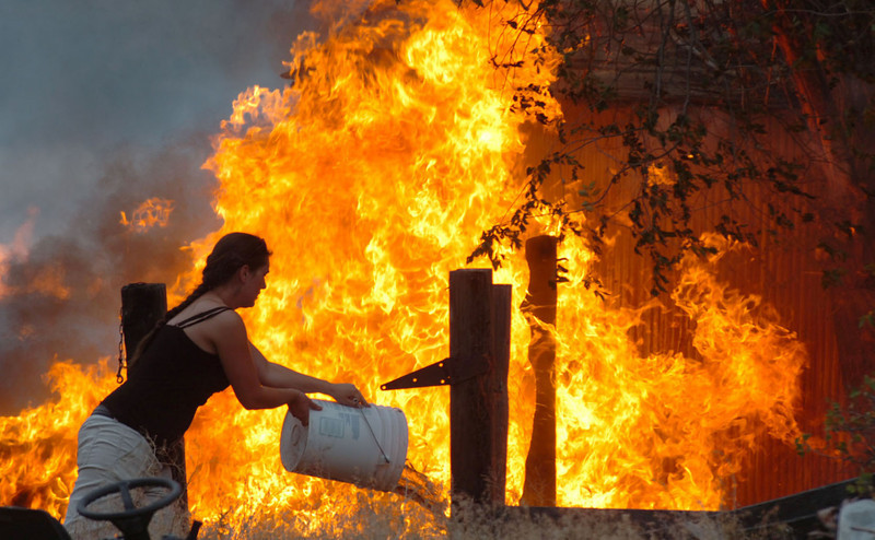 An unidentified woman throws a bucket of water on an out of control fire as it engulfs an outbuilding prior to the arrival of Bureau of Land Management firefighters and Pocatello Valley Fire District firefighters on the scene Friday evening, July 6, 2007 just outside of Pocatello, Idaho. The fire was named the Gap Fire by the BLM. AP Photo/Idaho State Journal, Bill Schaefer(IDPOC101).