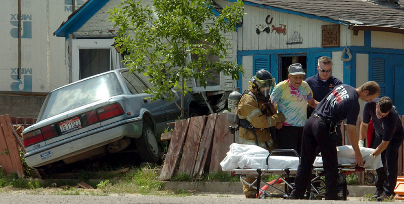 Journal photo by Bill Schaefer<br /> EMT's and a Pocatello fireman help Tony Gonzales to a gurney after a car crashed into his home at 12 W. Terry Wednesday afternoon, June 7, 2006. Gonzales was uninjured and later released from the hospital.