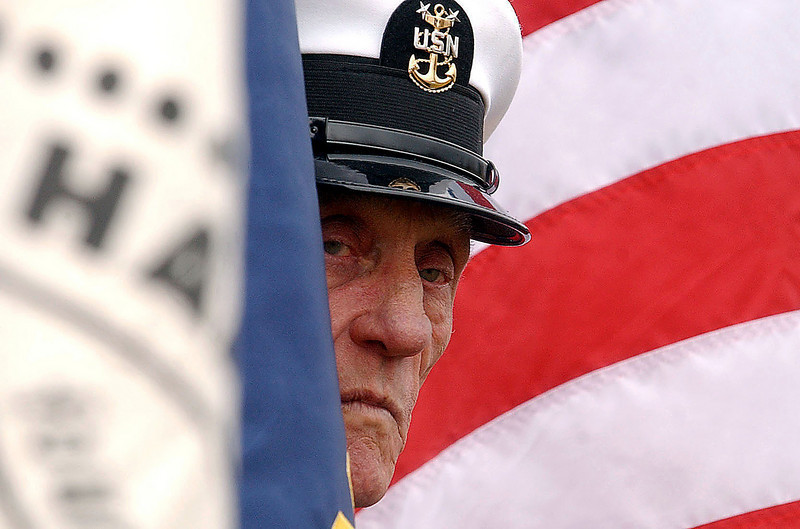 Navy veteran Jim Clarke waits for the Veteran's Day ceremonies to commence at Irving Middle School's football field.