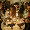 Families gather around as the children light the Menorahs during the Hanukkah celebration Saturday evening.