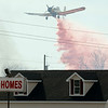 A crop duster plane drops flame retardant on the burning field behind R/C Homes Sale's lot Friday afternoon.