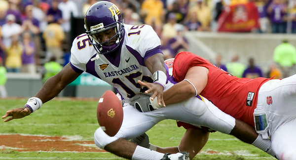 East Carolina quarterback Patrick Pinkney (15) loses the football while being sacked in overtime Saturday at N.C. State's Carter-Finley Stadium. The Wolfpack recovered the fumble, then scored on its possession to win the game, 30-24.