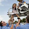 Fire-rescue trainees lift up pediatric patient Serena Ortiz to check out the view from the rescue truck ladder Friday afternoon at PCMH.  The trainees were surprised with the visit to the Children's Hospital during their vigerous training schedule.