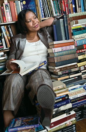 Author Pansy Flood hangs out with a stack of books in the Tipsy Teapot while shooting the Her Magazine cover.  (Jenni FArrow)