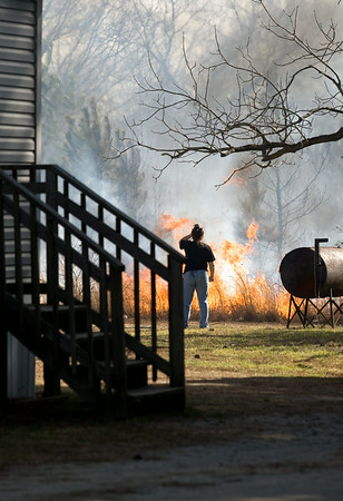 A woman watches as the brush fire moves to the area behind her home along 264.  Later she reported her home was unharmed and was thankful that no one was injured in the blaze.