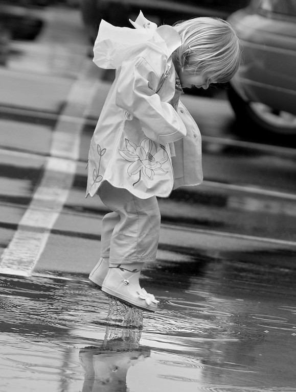 Kenley Riley, 2, would probably tell you her favorite part of Kidsfest Saturday afternoon, was the rain puddles.  The sport of recreational  puddle jumping was a new freedom for Kenley after getting a new rain slicker and boots.  (Jenni Farrow)