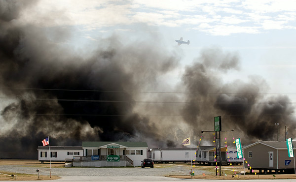 A plane flys over Welcome Homes Sales lot on Hwy 264 towards Washington where a brush fire, suspected of being started by a cigarette discarded along the highway, claimed units in the rear of the mobile home sales lots.